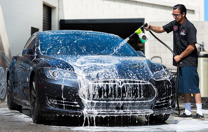 TONY'S ELITE MOBILE DETAILING expert wearing black shirt washing black car with hose spray