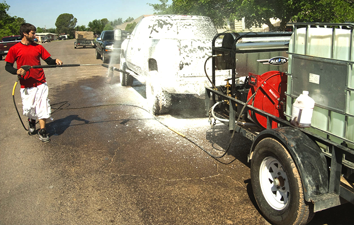 TONY'S ELITE MOBILE DETAILING expert wearing red shirt washing black SUV with Foam Cannon